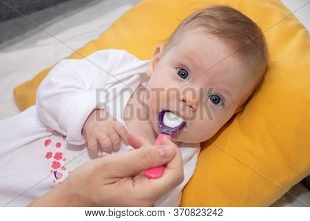 Cute Little Baby Girl Lying On The Bed And Eating Rice Soup With Spoon. Mother Feeding Her Baby Girl