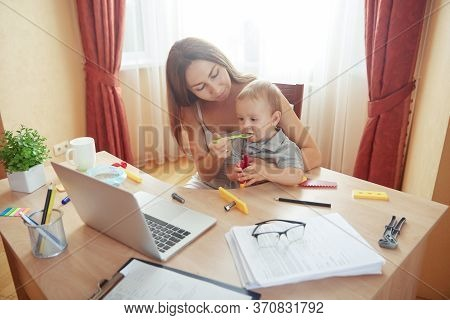 Mother Feeding Baby With Solid Food Nutrition From Spoon During Online Work Break Time In Home Offic