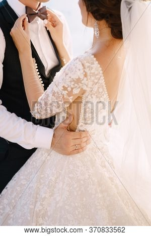 A Closeup Of The Hands Of A Bride. He Plays With His Fingers With A Grooms Bow Tie. The Groom Hugs T