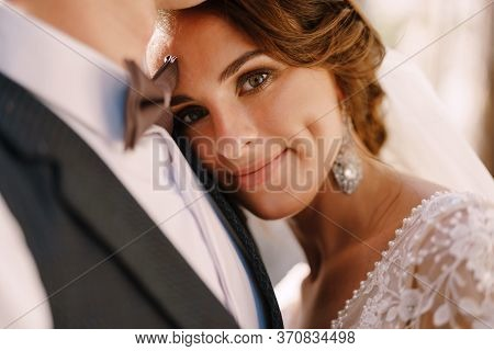 Close-up Portrait Of A Bride Looking At The Camera, Laid Her Head On The Grooms Chest. Beautiful Wed
