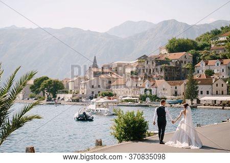 Fine-art Wedding Photo In Montenegro, Perast. A Wedding Couple Walks Along The Promenade Near The Se