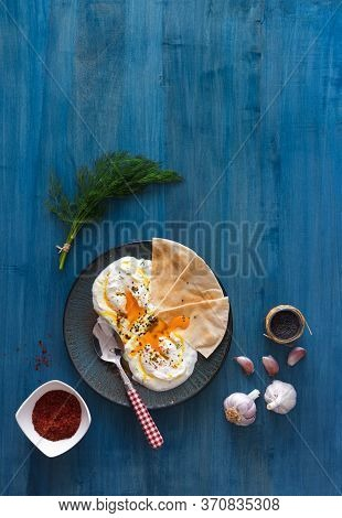 Dish With Turkish Eggs Cilbir, Plain Yogurt, Poached Eggs, Garlic, Chilli, Fresh Dill And Melted But