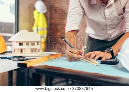 Engineers Holding A Pen Pointing To A Building And  Drawing Outlay Construction Plan As Guide For Bu