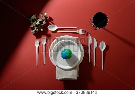 Serving Table With Earth Planet, Plastic Plates, Spoons, Forks, Knives, Serviette, Flowers And Wine