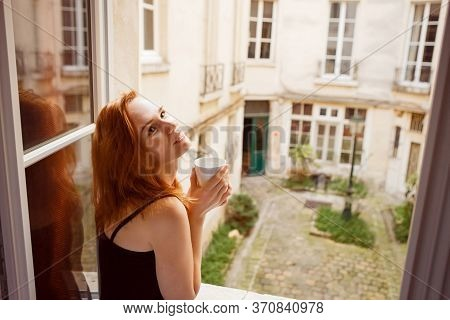 Woman Drinking Coffee In The Morning By The Window Overlooking The Inner Courtyard Of The French.