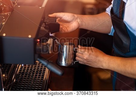 Barista Steaming Milk In The Pitcher With Coffee Machine For  Preparing To Make Latte Art.