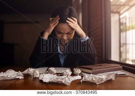 Businesswoman Sitting With Head In Hands At Desk And Crumpled Papers.