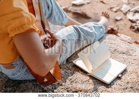Notes,lyrics In The Book On Stone At Parks Beside Women Play Guitar.