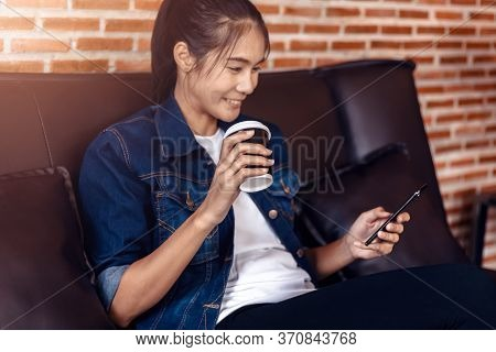 Happy Woman's Hands Holding Mobile Phone And Coffee Cup In Cafe And She Sitting On Sofa.