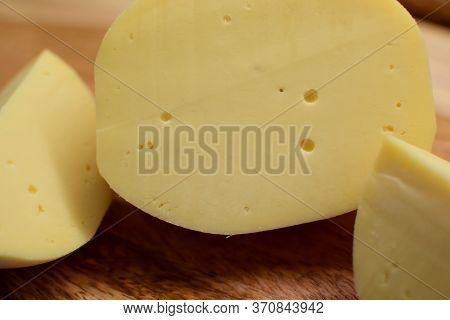 Edam Yellow Cheese Is Located On A Wooden Board.