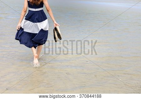 Woman Barefoot Hold Her Shoes Walking On Summer Along Wave Of Sea Water And Sand On The Beach.