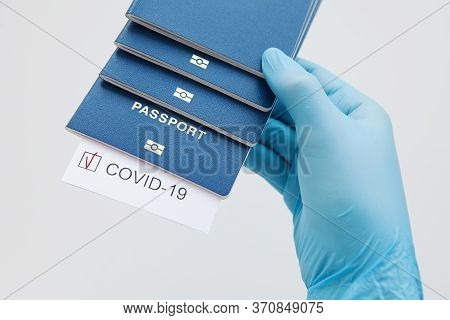 Immunity Passport, Risk-free Certificate Concept. Hand In Medical Glove Hold Passports With Note Cov