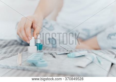 Young Woman Making A Manicure Herself With Nail Varnish Because Of The Coronavirus Epidemic. Home Li