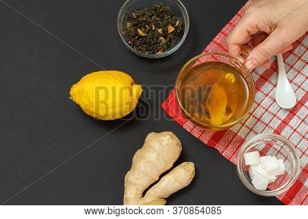 Health Remedy Foods For Cold And Flu Relief With Lemon, Ginger And Tea On A Black Background. Female