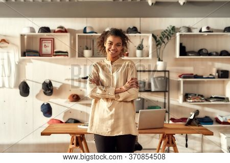 Portrait Of Young Smiling Female Worker Looking At Camera While Standing In The Office. Woman Workin