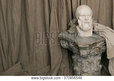 Plaster Bust Of Socrates On A Background Of Beige Fabric