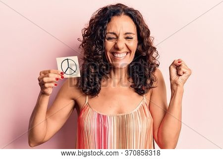Middle age beautiful woman holding peace symbol reminder screaming proud, celebrating victory and success very excited with raised arm
