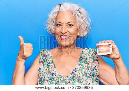 Senior grey-haired woman holding denture smiling happy and positive, thumb up doing excellent and approval sign