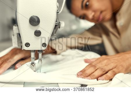 Close Up Of Seamstress Sitting And Sewing. Dressmaker Working On The Sewing Machine. Tailor Making A