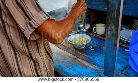Indonesian Food, Mie Ayam, Noodles With Chicken Presented Directly By The Seller On The Cart, Unfocu