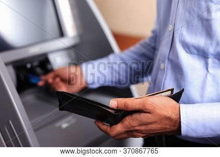 Man With An Open Black Wallet At Atm Machine, Inserting A Credit Card. Atm Transaction. Close Up. So
