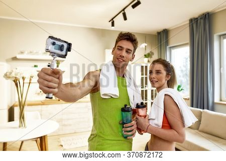 Young Couple In Sportswear Recording Video Blog Or Vlog About Healthy Lifestyle On Camera After Exer
