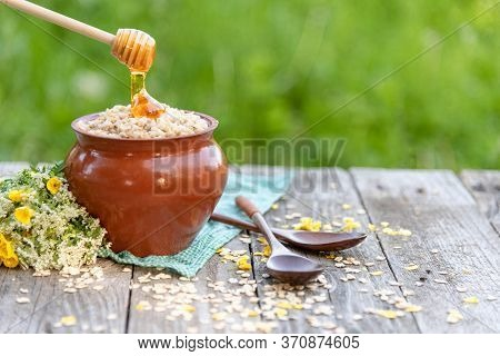 Oatmeal Porridge In A Pot With Honey. Natural Rustic Porridge In The Fresh Air.