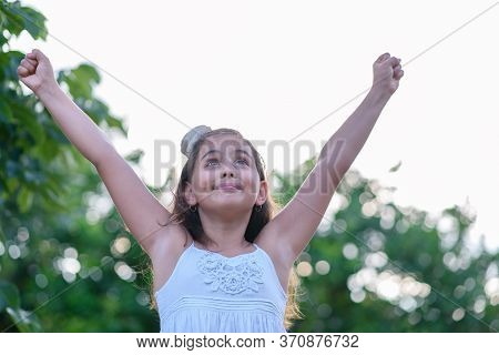 Victorious Girl Celebrating With Her Arms In The Air. Achievement, Success And Victory Concept.