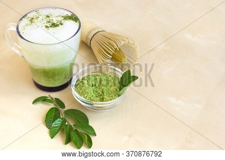 Matcha Latte Green Tea Cup Light Background. Matcha Powder, Green Tea Leaves And Bamboo Whisk. Space