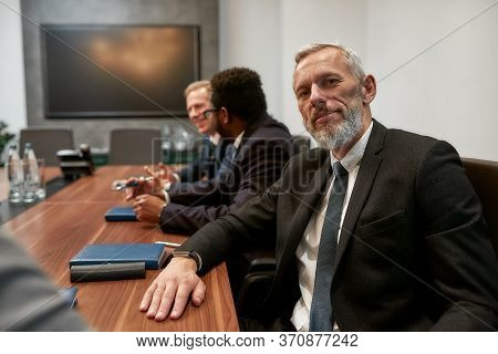 Portrait Of Bearded Mature Man In Formal Wear Looking At Camera While Sitting At The Office Table Wi