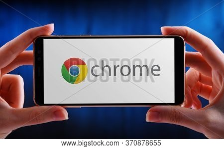Hands Holding Smartphone Displaying Logo Of Google Chrome