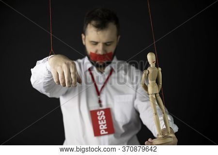 Man With Badge Press Holds Hands Tied With Ropes Like Marionette With Wrapping Mouth By Adhesive Tap