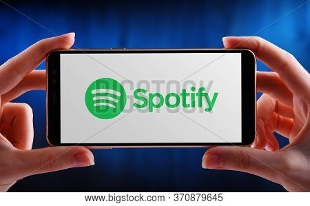 Hands Holding Smartphone Displaying Logo Of Spotify