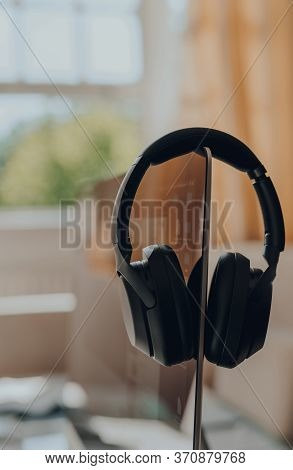 Close Up Of Black Over Ear Headphones Hanged On A Monitor, Selective Focus, Work From Home Concept.