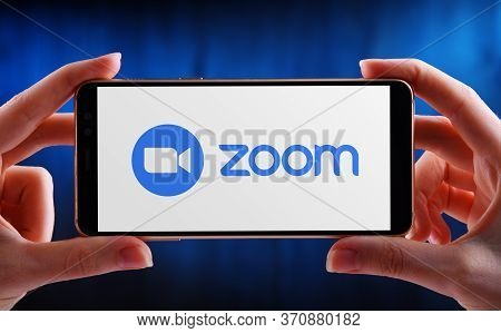 Poznan, Pol - May 21, 2020: Hands Holding Smartphone Displaying Logo Of Zoom, Videotelephony And Onl