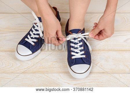 Caucasian Woman Hands Tie White Elastic Laces On Classic Blue Sneakers Or Gumshoes Indoor. Comfortab