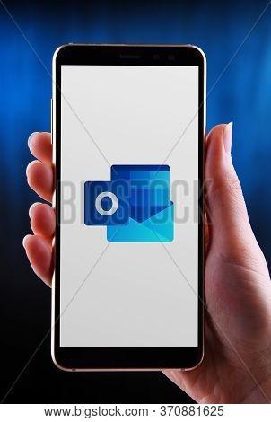 Poznan, Pol - May 21, 2020: Hands Holding Smartphone Displaying Logo Of Microsoft Outlook Program, P