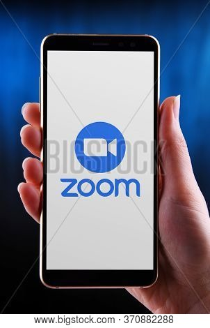 Hands Holding Smartphone Displaying Logo Of Zoom