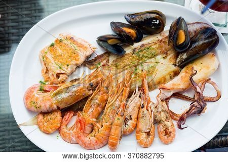 Seafood With Fish, King Prawns, Mussels And Octopus On A White Plate. Table Setting. Restaurant Food