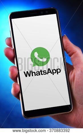 Hand Holding Smartphone Displaying Logo Of Whatsapp Messenger
