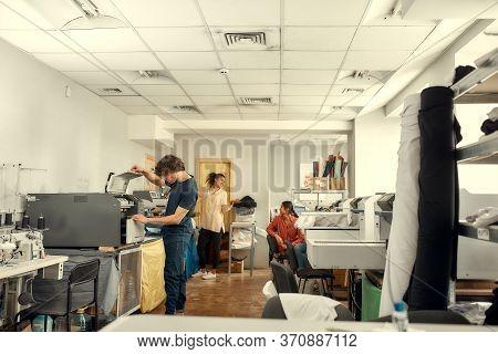 Full-length Shot Of Young Cheerful Millennials Using Heat Press Transfer, Silk Screen Printing Machi