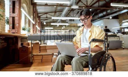 Portrait Of Young Male Office Worker In A Wheelchair Looking At The Screen Of His Laptop While Perfo