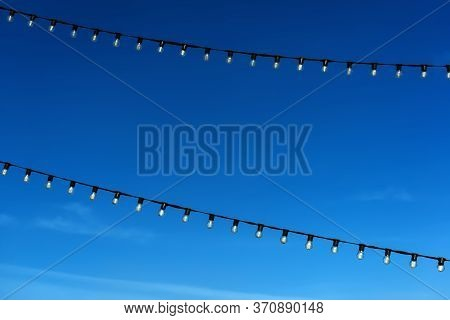 Two Garlands Of Filament Lamps With A Dark Blue Sky Background