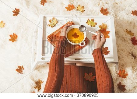 A Female Sits On A Cream Rug With A  Bowl Of Spiced Pumpkin Rich And Thick Home Made Soup.  Seasonal