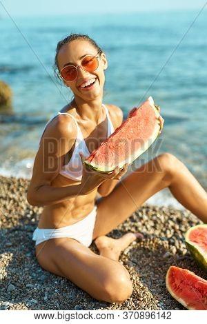 Tanned Joyful Girl In White Bikini And Sunglasses Holding Huge Slice Of Watermelon Sitting On Sea Be