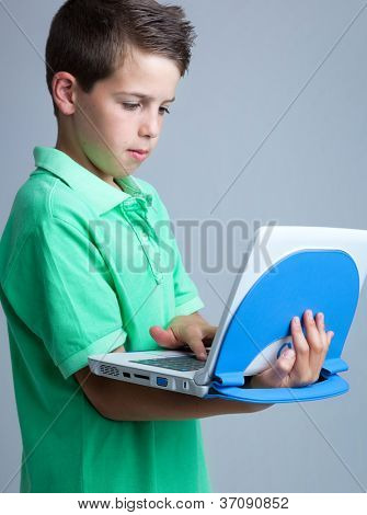 Boy with laptop on grey background