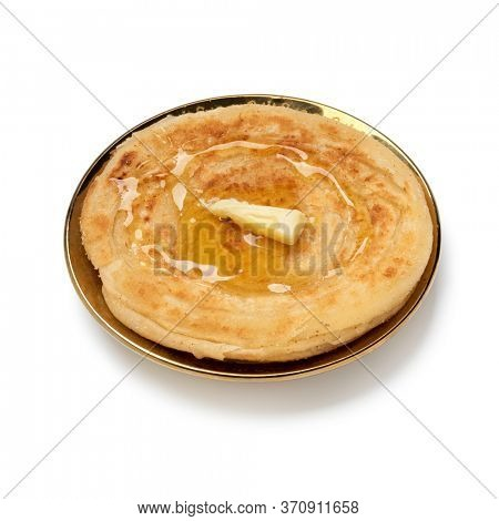Single fresh baked meloui, Moroccan pancake with butter and honey close up isolated on white background