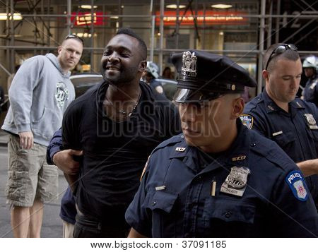 NEW YORK - SEPT 17: An unidentified man smiles as he is arrested on the 1yr anniversary of the Occupy Wall St protests on September 17, 2012 in New York City, NY. Attempts to elude police were futile.
