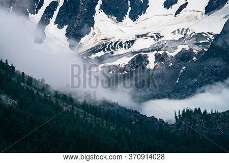 Bleak Dramatic View To Giant Snowy Mountain Wall Among Low Clouds At Dark Evening. Gloomy Alpine Lan