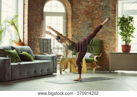 Balance. Sporty Beautiful Young Woman Practicing Yogas Asanas Professionally At Home. Concept Of Hea